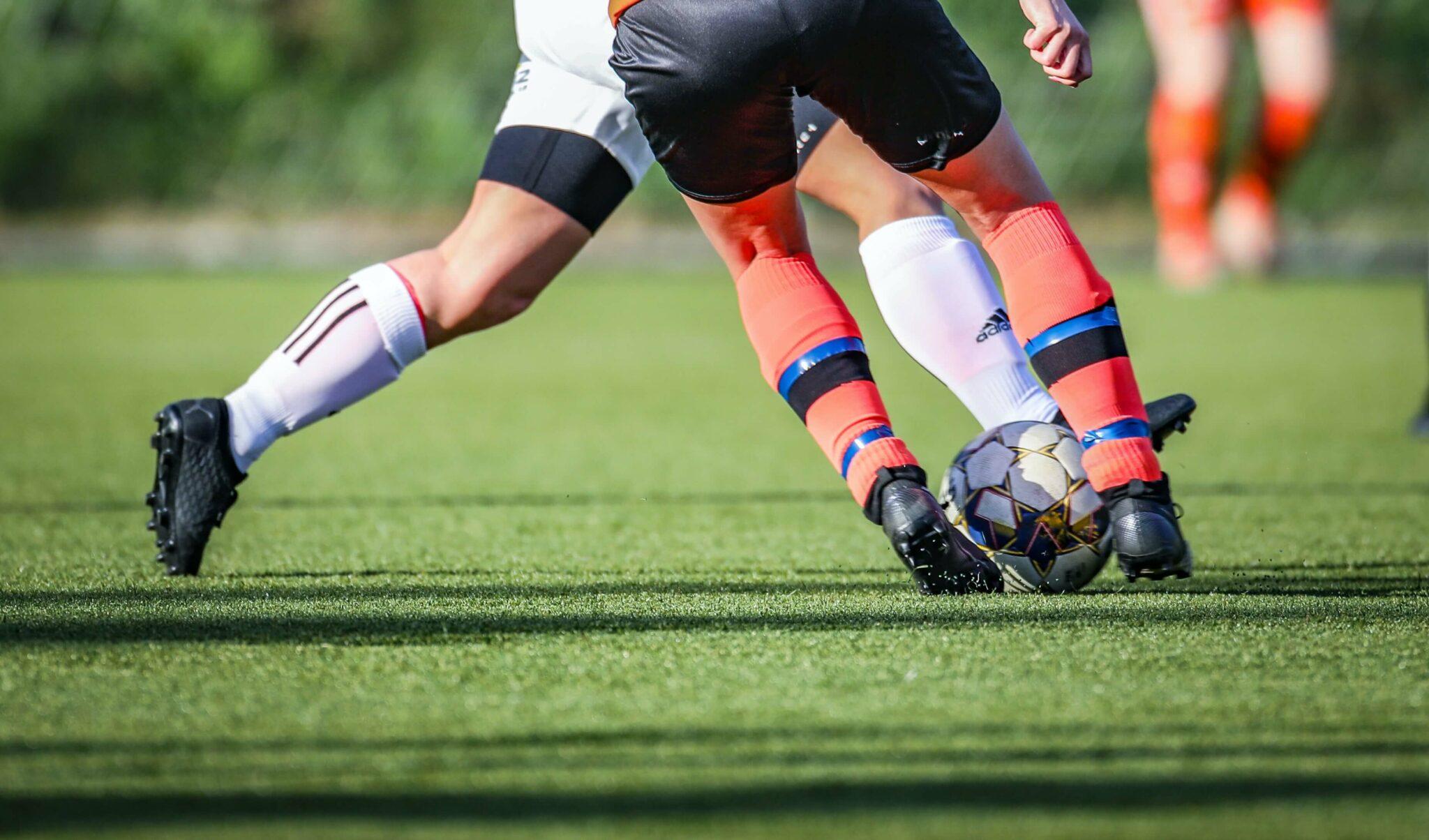 Två fotbollsspelare i närkamp om fotboll